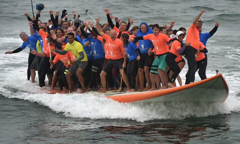 World Record Set When 66 People Ride One Surfboard At The Same Time